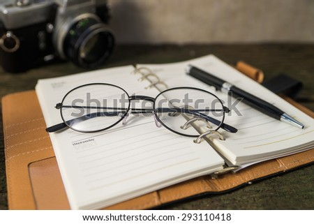 mock up eyeglasses notebook pen and camera on wood background. concept relax time at work.depth of field.vintage color  - stock photo