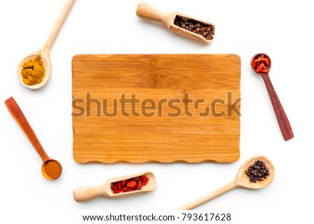 Mock up for menu or recipe. Wooden cutting board near scoops and spoons with spices on white background top view
