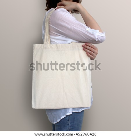 Mock-up. Girl is holding blank cotton tote bag. Handmade eco shopping bag for girls.