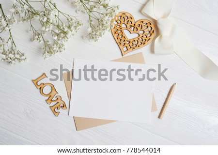 Mock up letter with a love box in the shape of a heart lies on a wooden white table with gypsophila flowers, a greeting card for Valentine's Day with a place for your text. Flat lay, top view photo.