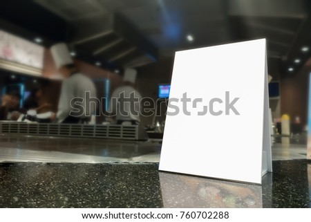 Mock up Menu frame on Table in Bar restaurant ,Stand for booklets with white sheets of paper acrylic tent card on cafeteria blurred ,Chef cooking in background.