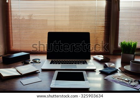 Mock up of business person luxury accessories and work tools, cup of american coffee, sunglasses, notepad, money bills, envelope, digital tablet and laptop computer, hipster office workplace desktop  - stock photo
