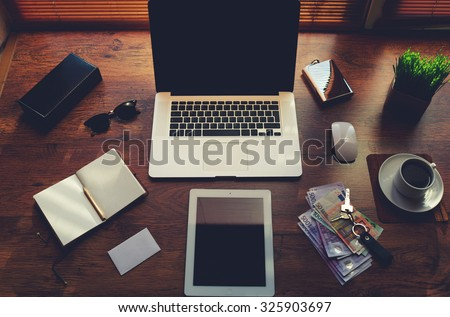 Mock up of freelancer desktop with luxury accessories and work tools, cup of coffee, sunglasses, open notepad, money bills, envelope, digital tablet and laptop computer, hipster office workplace