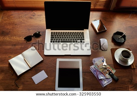 Mock up of hipster office workplace with luxury accessories and work tools, cup of coffee, sunglasses, open notepad, money, mouse, envelope, digital tablet and laptop computer with copy space screen