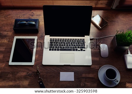 Mock up of office or home desktop with gadgets and work tools, blank screen portable laptop computer, mouse, sunglasses, digital tablet, empty touch pad, white envelope, modern hipster workspace - stock photo