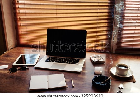 Mock up of successful person with luxury accessories and work tools, cup of american coffee, open notepad, money, envelope, digital tablet and laptop computer, hipster office workplace desktop  - stock photo