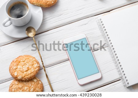 Mock up of white smart phone on a cafe desktop among cookies with coffee cup. Clipping path included.