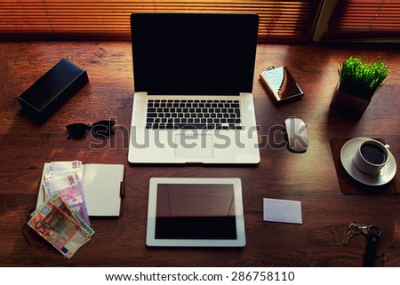 Mock up of workspace with laptop computer and digital tablet, electronic business and distance work concept, successful businessman or entrepreneur wooden table with style accessories and euro bills - stock photo