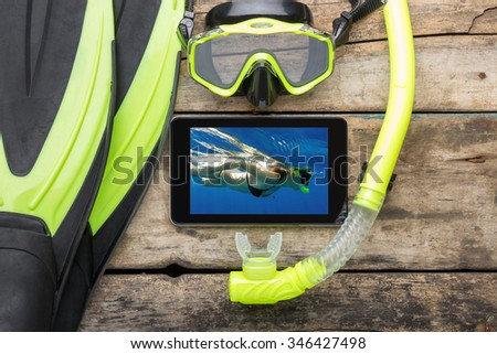 Mock-up snorkelling equipment with tablet PC on wooden background. Flippers, mask and snorkel with remembrance of summer holidays - stock photo