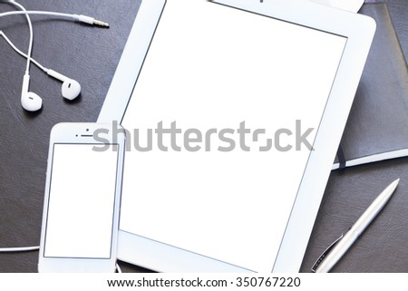 mock up with modern white smartphone and tablet  on black desk - stock photo