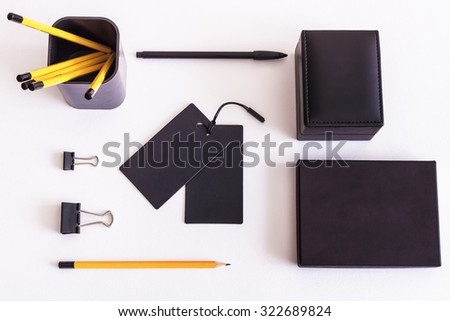Mockup. Black leather box, black shopping tags and pencils on a white background.