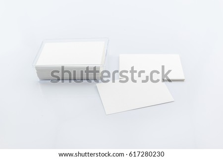 Mockup of blank white business cards on light grey background. Business cards typically include giver's name, company or business affiliation with logo and contact information i.e. street address, etc