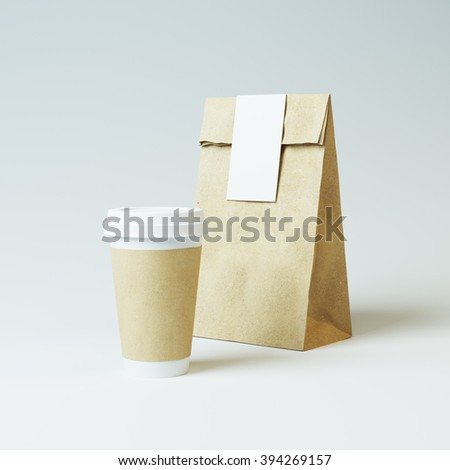 Mockup of craft paper bag and cup on light background