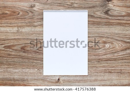 Mockup of open album with blank white page on wooden background. Vertical orientation, top view. - stock photo