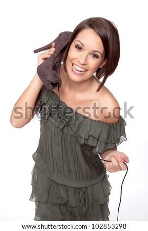 model acts like she is make a phone call using her shoe, symbolizing for example that she loves shoes or that she is ordering new shoes. - stock photo