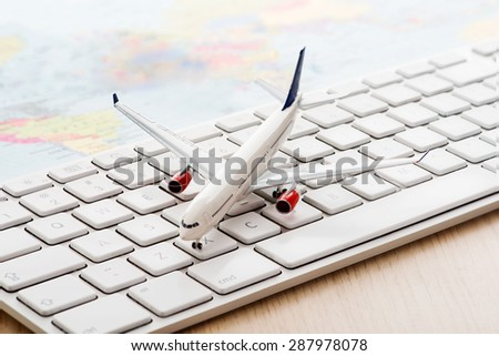 Model airplane on computer keyboard - stock photo