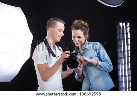 Model and photographer looking at made photo and smiling