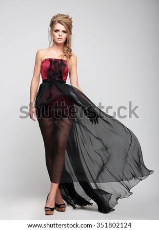 Model blonde girl in long dress on grey background. - stock photo