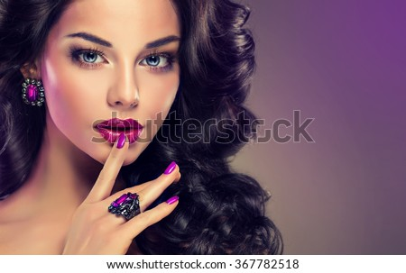 Model curly hair and jewelry , violet makeup , manicure on nails .  elegant hairstyle . Fashionable jewelry set , ring and earrings . - stock photo