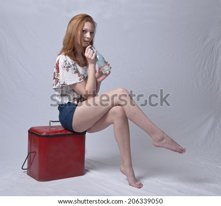 Model drinking soda while sitting on retro cooler. - stock photo