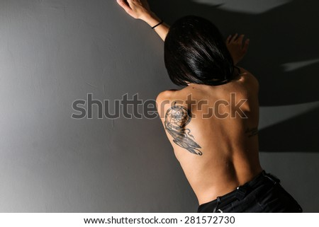 Model from behind, standing against a dark wall, showing her tattoo against envy people - stock photo