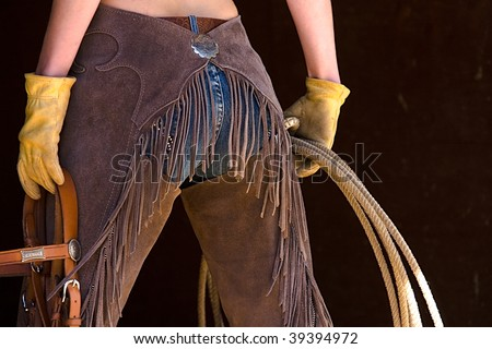 Model holding lasso wearing chaps - stock photo