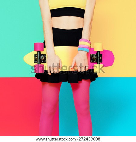 Model holding Skateboard on bright exclusive batskground - stock photo