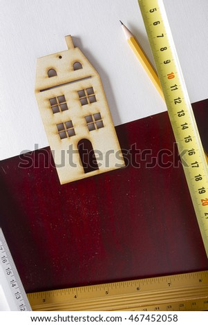 Model house and drawing tools on a wooden table