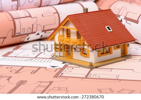 model house on architectural blue print plan - stock photo