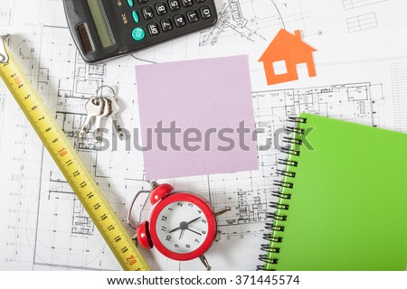 Model house on construction plan for house building, keys, red alarm clock and calculator. With pink blank business card. Real Estate Concept. - stock photo
