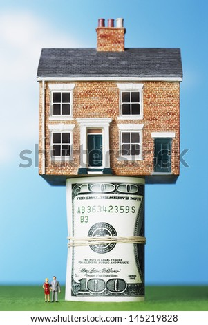 Model house on roll of $100 notes - stock photo