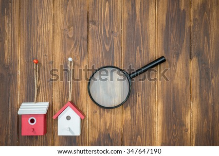model house with Magnifying Glass on wooden background, House hunting - stock photo