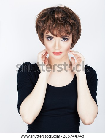 Model in black dress. Fashion portrait of beautiful young woman with short hair dress. Studio posing sexy woman.