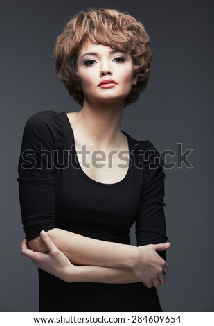 Model in black dress. Fashion portrait of young woman. Studio posing sexy woman.