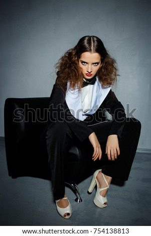 Model in black stylish suit with red lipstick