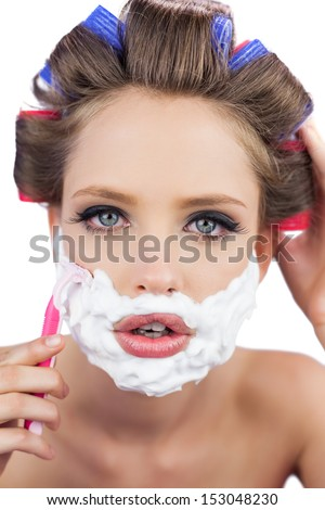Model in hair curlers posing with shaving foam and razor in close up on white background - stock photo