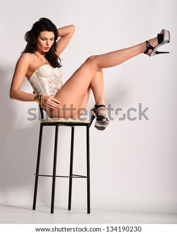 Model in lingerie sitting on high chair - stock photo