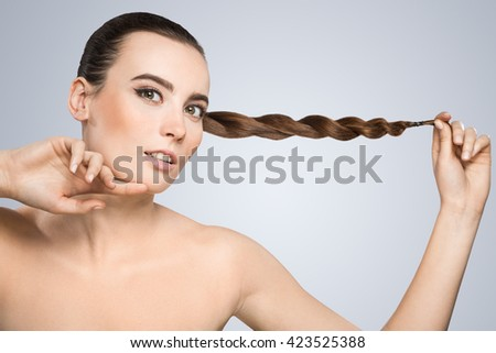 Model looking at camera and touching her chin. Nice make-up, looking lively with light smile. Holding pigtail aside. Beauty portrait, head and shoulders. Indoor, studio - stock photo