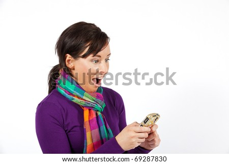 Model looking surprised at her cell phone - stock photo