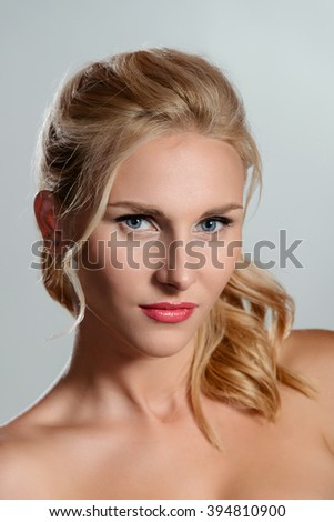 Model looks straight in the camera. Very beautiful hairstyle and ideal skin. Tender bare shoulders. Bright lipstick. - stock photo