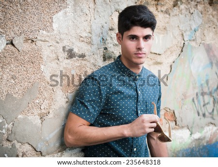 Model man holding a sunglasses outdoors over ruinous wall - stock photo