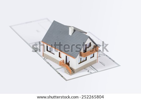 Model of a family house on a blueprint. - stock photo