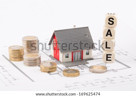 Model of a family house on a blueprint for sale - surrounded by Euro coins - stock photo