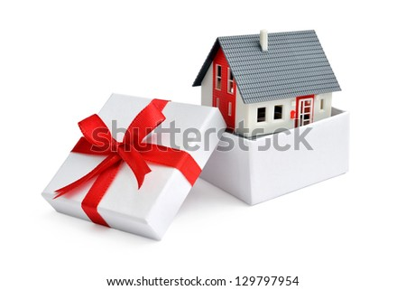Model of a house in gift box with red ribbon - stock photo