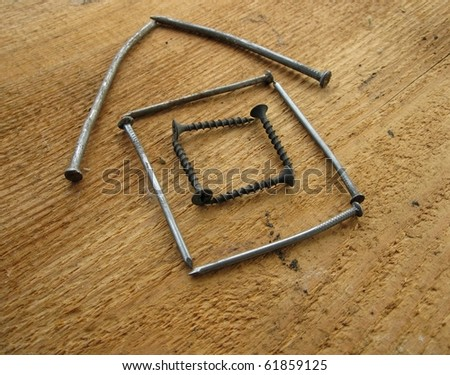 Model of a house made from nails on wood board - stock photo