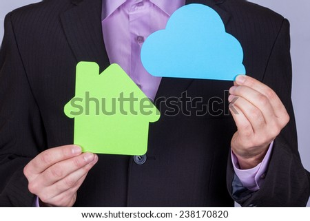 Model of a private house in the hands of men. A man in a business suit with a model house and cloud. The concept of smart homes, home control with digital technology. - stock photo