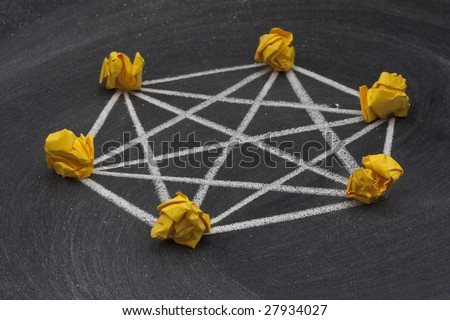 model of fully connected (mesh)  network made with yellow crumbled paper nodes, white chalk connection lines and blackboard with eraser smudges in background
