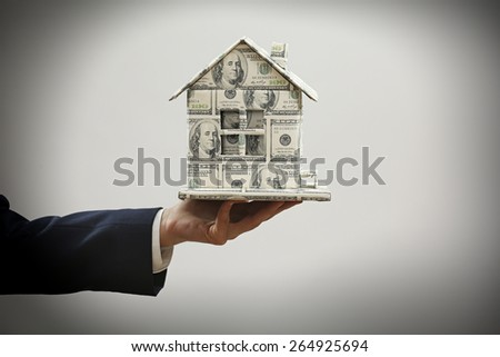 Model of house made of money in male hand on gray background - stock photo