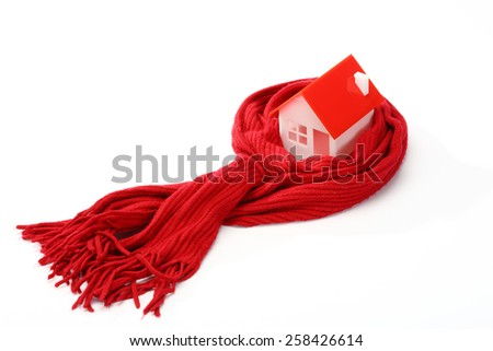 Model of house wrapped in red scarf over white