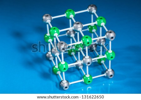 Model of molecular structure on blue reflective background - stock photo